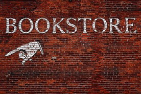 Direction to a bookstore painted on a brick wall