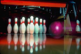 Bowling pins about to be hit by a bowling ball