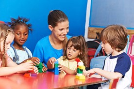 Child care provider and children playing with Lego