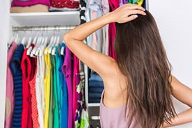 Girl selecting a dress from her closet