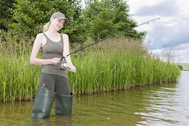 Fishing in a stream wearing hip boots