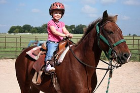 Child learning to ride a horse