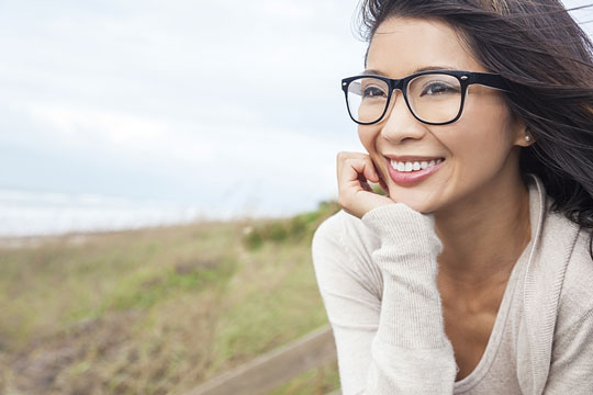 Smiling Asian woman with dark-rimmed eyeglasses