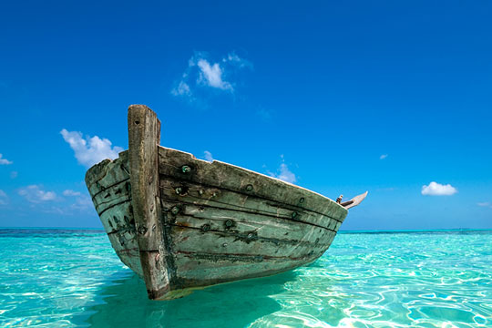 Old wooden boat floating on a tropical sea