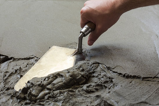 Spreading wet concrete with a trowel
