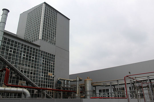 Factory with cloudy sky background