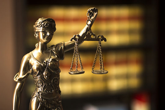 Blindfolded woman holding scales of justice