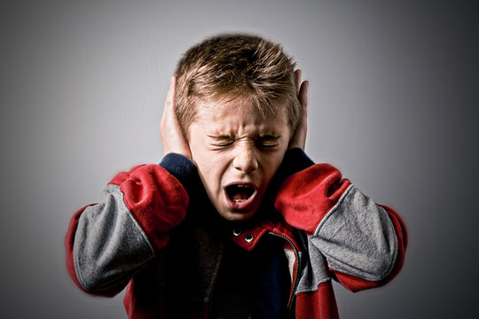 Child protecting his ears from loud noise