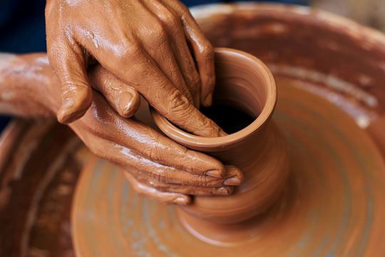 Potter forming pottery on a wheel